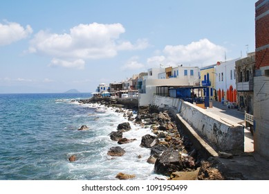 NISYROS, GREECE - JUNE 9, 2015: Tavernas line the rocky seafront at Mandraki on the Greek island of Nisyros. The island is best known for its still active volcano.