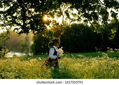 Nitaure, Latvia - june 23, 2009: A happy woman in a Latvian folk costume with a flower crown in her head is standing in a meadow, celebration of the midsummer holidays (Ligo) in Latvia.