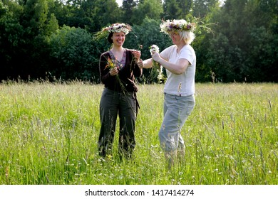 Nitaure, Latvia - june 23, 2009: Women make a flower crown in a flower meadow. celebration of the midsummer holidays (Ligo) in Latvia.