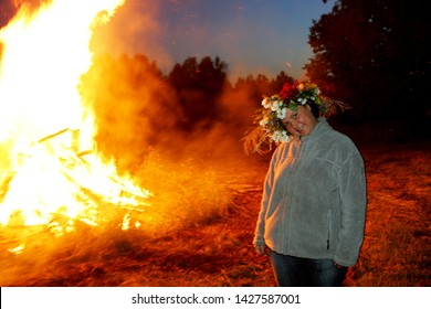 Nitaure, Latvia - june 23, 2009: A young happy woman with a flower crown on a head standing at a large campfire at ligo night. LIGO - Midsummer night celebrating in Latvia