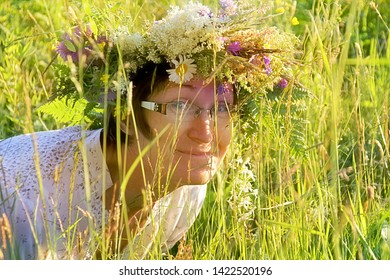 Nitaure, Latvia - june 23, 2016:  Women with flower crowns in the head sits in a flower meadow and smells of nightlily flower. Old Latvian culture tradition. Midsummer night celebrating in Latvia.