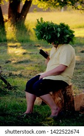 Nitaure, Latvia - june 23, 2016: A man with an oak crown in his head sits at a campfire and watches a cell phone. Old Latvian culture tradition LIGO. Midsummer night celebrating in Latvia.