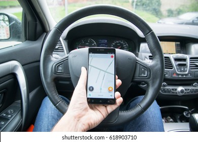 Nitra, Slovakia, april 7, 2017: Driver holding smartphone with Waze navigation application behind the driving wheel in car