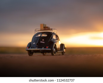 NITRA, SLOVAKIA - JUNE 28 2018: Volkswagen Beetle with suitcases on the roof by sunset. Sunset over Volkswagen Beetle. Classic car VW Beetle by summer sunset. Back view.