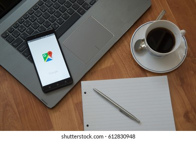 Nitra, Slovakia, march 28, 2017: Google maps application in a mobile phone screen. Workplace with a laptop, an earphones, notepad, pen and coffee on wooden background