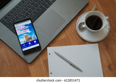 Nitra, Slovakia, march 28, 2017: Wizzair application in a mobile phone screen. Workplace with a laptop, an earphones, notepad, pen and coffee on wooden background