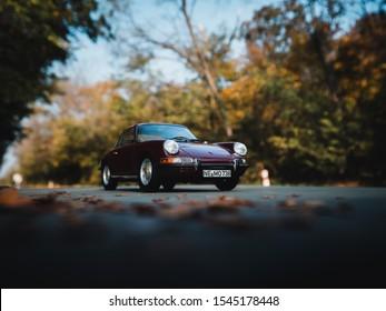 NITRA, SLOVAKIA - OCTOBER 27 2019: Porsche 901/911 on autumn road. Porsche 901/911 and falling leaves. Scale model Porsche 1:18. Classic car on autumn road.