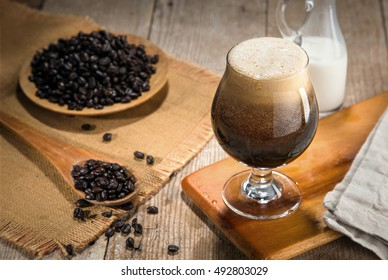 Nitro coffee nitrous infused delicious serving in tulip glass with coffee bean wooden table