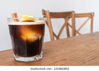 nitro cold brew coffee with ice, cinnamon and lemon on wooden table and chairs set as a special drink menu ready to serve for the client on the coffee shop. cold drink coffee and business concept.
