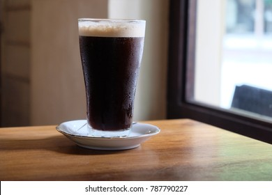 Nitro cold brew coffee with white fluffy head. The coffee filled in a tall glass, placed by the window with sunlight.