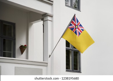 Niue flag hanging on a pole in front of the house. National flag waving on a home displaying on a pole on a front door of a building and raised at a full staff.