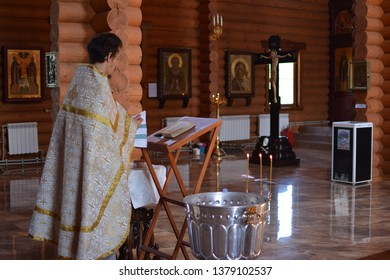 NIZHNIY NOVGOROD, RUSSIA June 4th 2016 inside the wooden Russian Orthodox Church with many icons on the altar, the rite of baptism is held by a priest praying and reading the Bible