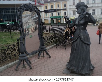 Nizhniy Novgorod, Russia - Oct 2013: street sculpture of young pretty lady looking at herself at mirrow