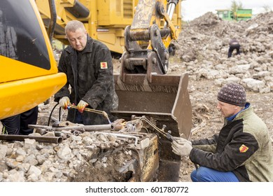 NIZHNY NOVGOROD, RUSSIA  3 FEBRUARY 2015: Working people, blowtorch and toolbox repair the chassis in an excavator. Russia .