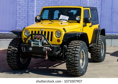 Nizhny Novgorod, Russia April 14, 2018: Solemn opening of the salon for the sale of automobiles. Jeep 'Wrangler Rubicon' with large out-of-road wheels, Yellow. The inscription: on the glass: the buyer