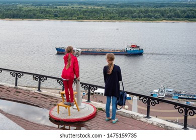 Nizhny Novgorod, Russia, - July 17, 2019 View from the right bank of the Volga River, little girl looks at the ships on the Volga from the observation deck above the Chkalov stairs.