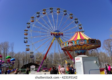 """Nizhny Novgorod, Russia - May 2.2013. Ferris wheel in the park """"Switzerland"""". On a warm spring day, the townspeople with children having fun ride on the carousel."""