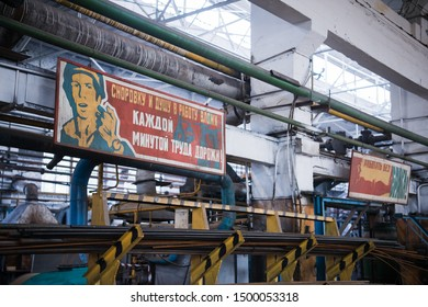 NIZHNY NOVGOROD, RUSSIA - OCT 7, 2017: Abandoned industrial complex. Big soviet russia motivational posters at factory. Remains of Communism