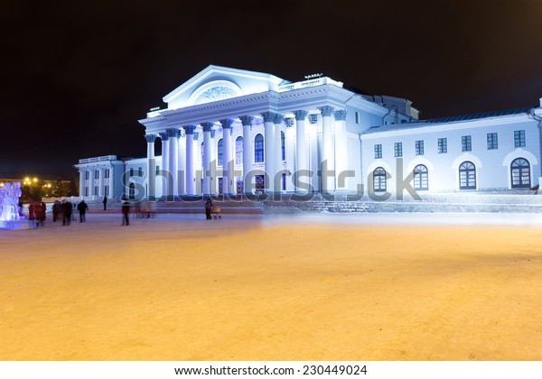 NIZHNY TAGIL, RUSSIA - JANUARY 01, 2014: Recreation center with night christmas illumination. People walk on the area in anticipation of the presentation