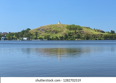 Nizhny Tagil, Russia. Lisya Hill with Watchtower reflected in the water of the city pond. The Watchtower is a symbol of Nizhny Tagil. It was built in 1818 in the Classical style.