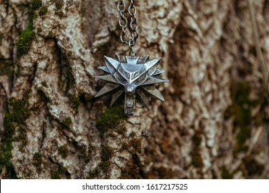 """Nizhyn, Ukraine/15 January 2020: Medallion of Geralt from School of White Wolf on wooden background. New Netflix premiere of TV series """"The Witcher"""" concept"""