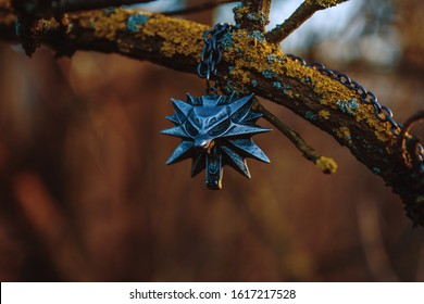 """Nizhyn, Ukraine/15 January 2020: Witcher's Geralt medallion of School of White Wolf on the tree. New Netflix premiere of TV series """"The Witcher"""" concept"""
