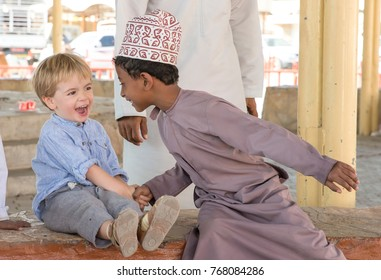 Nizwa, Oman, 10th Nobember 2017: kids of different origin at a market greeting each others