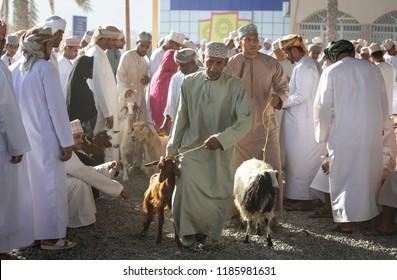 Nizwa, Oman, 21 September 2018: omani men at a market, buying and selling goats at a traditional habta auction