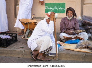 Nizwa, Oman, 21 September 2018: omani man selling dry fish and dates at a friday market. Sign in Arabic reads: selling in this area is strictly prohibited