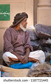 Nizwa, Oman, 21 September 2018: omani man selling dry fish and dates at a friday market