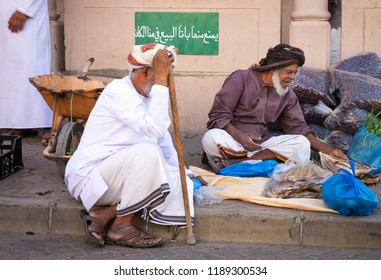 Nizwa, Oman, 21 September 2018: omani man selling dry fish and dates at a friday market. Sign in Arabic reads: 'selling in this area is strictly prohibited'