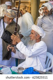 Nizwa, Oman, 24th March, 2017: omani man selling a hunting rifle at a market