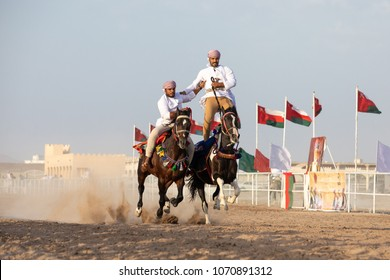Nizwa, Oman - Apr 13, 2018: Brave Omani men showing off their acrobatic riding skills on top of their fierce arabian stallions galloping at full speed on a dusty road.
