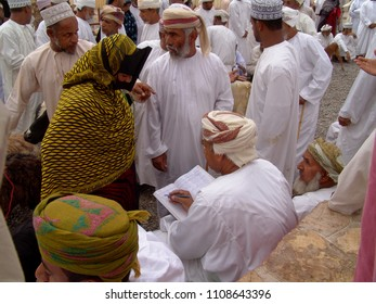 Nizwa, Oman - April 09, 2004: Accountant registeres sales and clients in a cash book on the goat market, surrounded by some clients in traditional Arabian dress - a woman in oman garb and some men