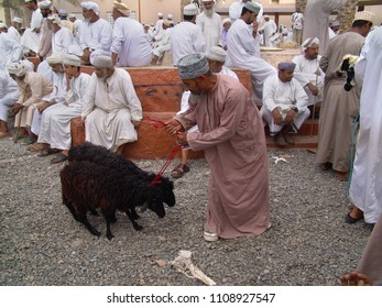 Nizwa, Oman - April 09, 2004: elderly man with friendly face in traditional omani dress tries to lead two black stubborn goats through the goat market