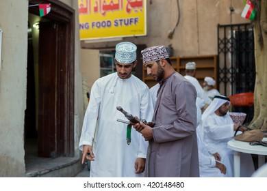 NIZWA, OMAN - APRIL 24 2015:Omani men at the traditional market or souq in Nizwa, Oman. It's a famous tourist sight seen in Nizwa, Oman.