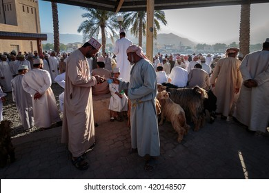NIZWA, OMAN - APRIL 24 2015:Omani men doing business at the traditional cattle market or souq in Nizwa, Oman. It's a famous tourist sight seen in Nizwa, Oman.