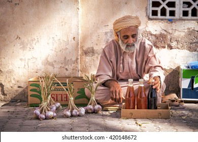 NIZWA, OMAN - APRIL 24 2015:Omani old man selling honey and garlic at the traditional market or souq in Nizwa, Oman. It's a famous tourist sight seen in Nizwa, Oman.
