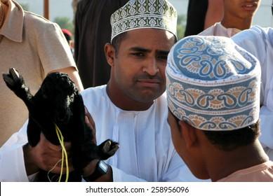 NIZWA, OMAN - DEC 28 2007:Omani men trade at the traditional Nizwa Cattle livestock market in Nizwa, Oman.It's a famous tourist sightseeing in Nizwa, Oman.