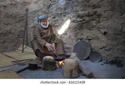 Nizwa, Oman, December 15th, 2016: Omani man roasting arabic coffee in a traditional house