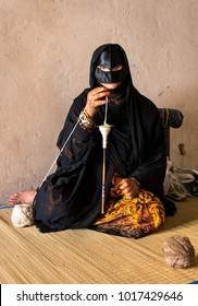 Nizwa, Oman, Febrary 2nd, 2018: old woman in full traditional outfit, spinning yarn