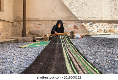 nizwa, Oman, Febrary 2nd, 2018: omani woman weawing a carpet