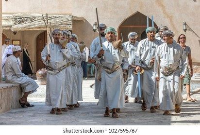 Nizwa, Oman, February 2nd, 2018: omani men in traditional clothing singing and dancing with swords
