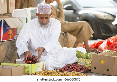 Nizwa, Oman, June 24th, 2017: omani man in traditional clothing selling new swason dates at a street market