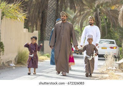 Nizwa, Oman - June 26th 2017: family  in traditional clothing at a toy market on a day of Eid al Fitr, celebration at the end of Holy Month of Ramadan