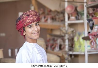 Nizwa, Oman, November 10th, 2017: omani boy dressed in traditional clothing, smiling for a camera