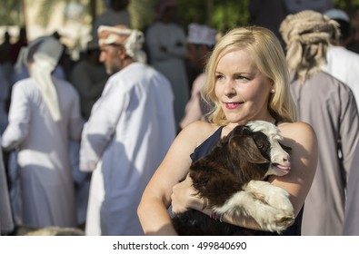 Nizwa, Oman, October 13th, 2016: young woman with a baby goat in Nizwa market at a goat market