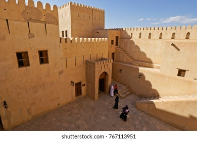 NIZWA, SULTANATE OF OMAN, FEBRUARY 21, 2013. Local people visit historic Nizwa Fort, built in the 17th century. Its tower dominates the town.