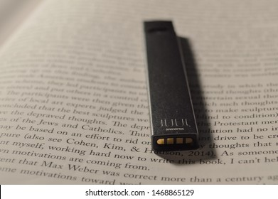 NJ / USA - July 28, 2019: controversial Juul placed on an open page of a textbook