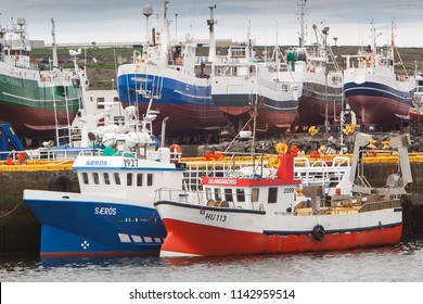 Njardvik / Iceland - July 26, 2018 : Fishing boats in Njardvik harbour with fishing boats on dry land in the background.